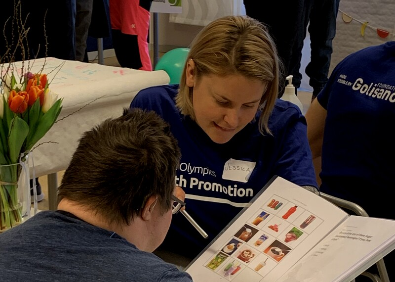 Health promotions volunteer showing an athlete literature.