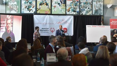 Two presenters on stage speaking to an audience with America football and Special Olympics materials displayed on the stage.