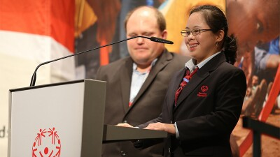 Special Olympics Athlete standing at podium with representative behind her.