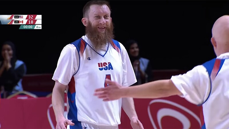 Athlete (in a USA jersey) on the court smiling as another player approaches him.