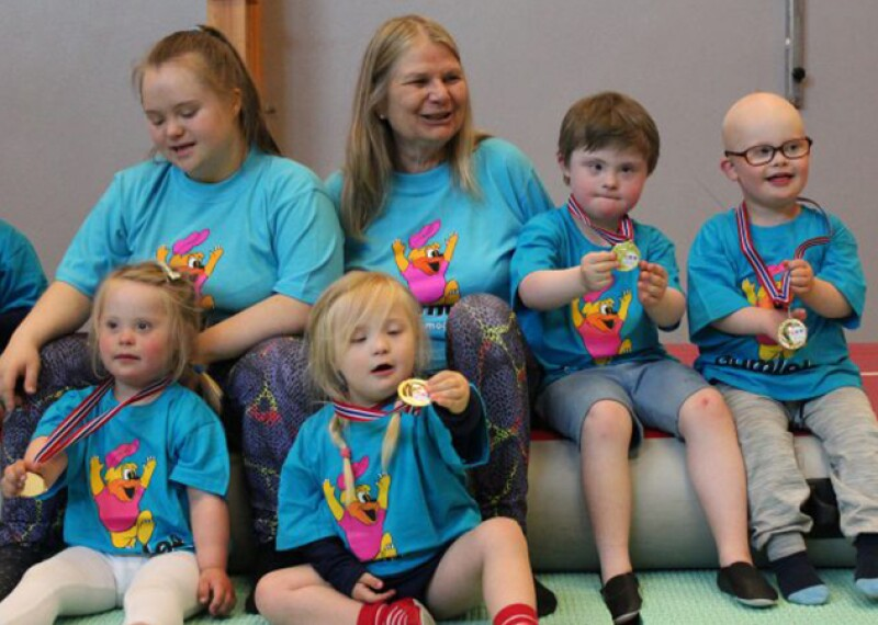 Two women sit among a group of children all wearing matching blue t-shirts.