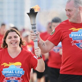 Sherrie and another runner hold the burning torch alongside side one another during the Final Leg.
