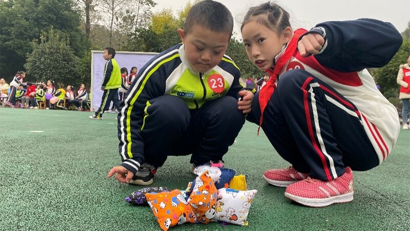 Two elementary school-aged students crouch on the field during their Unified challenge, which includes a pile of sacks. One student focuses on the pile of sacks while the other one points at the camera.