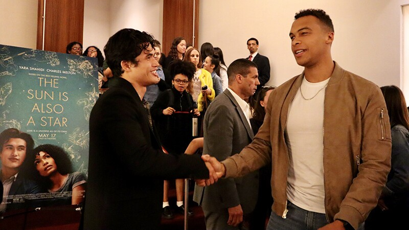 Charles Melton speaks with Dale Moss at a school.