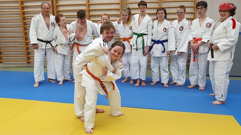 Two athletes demonstrating a move while the class observes.