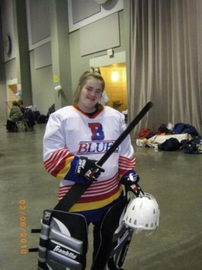 A Special Olympics athlete smiles at the camera while wearing goalie equipment for floor hockey.