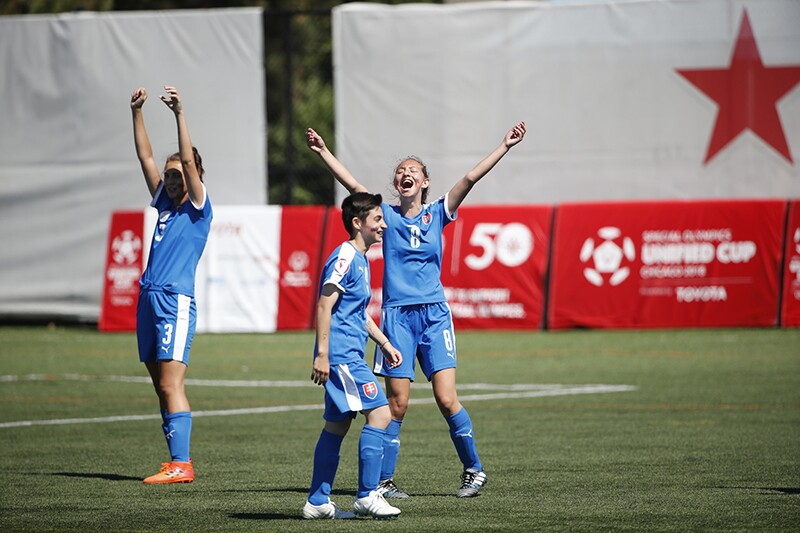 Three female football athletes on the field celebrating at the Unified Cup competition.