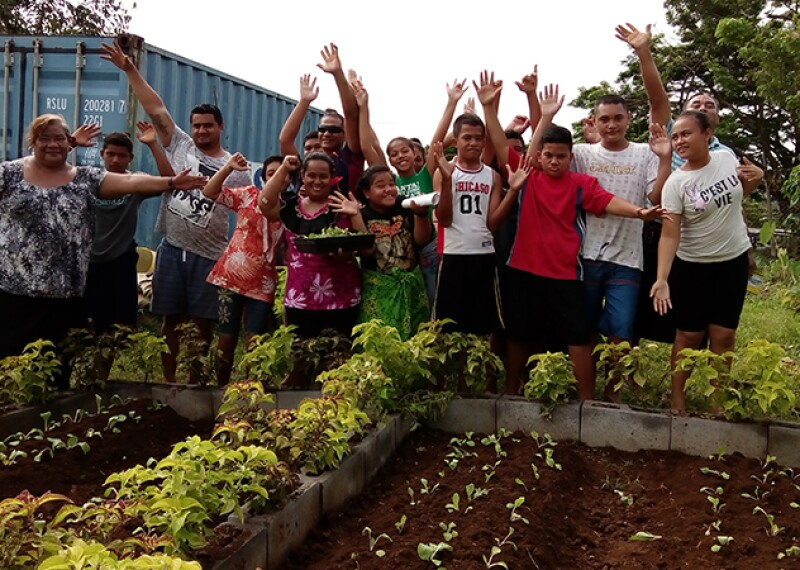 Group of people standing outside in front of a newly growing garden.