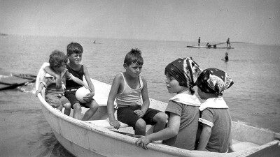 Black and white photo (ca. 1923-1924) of Eunice Kennedy Shriver and her siblings John F., Joe Jr., Rosemary and Kathleen in a boat at Cohasset, Massachusetts as a child sitting on a small boat with her siblings out in the water at Cohasset, Massachusetts.