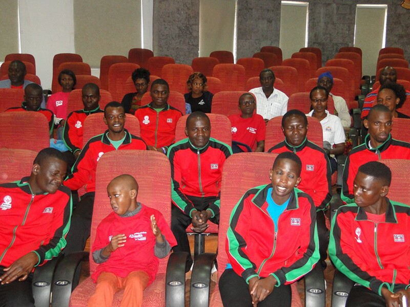 Group of athletes from Kenya sitting in theater seating.