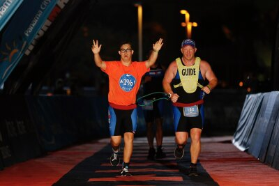 Chris Nikic and Dan Grieb cross the finish line at IRONMAN Florida in Panama City.