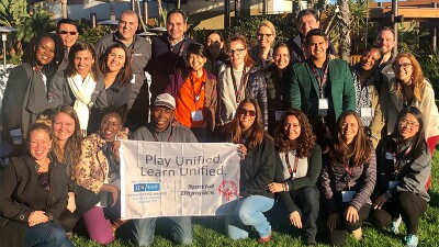 Special Olympics leaders gathered together in a group photo holding a Play Unified. Learn Unified, Special Olympics banner.
