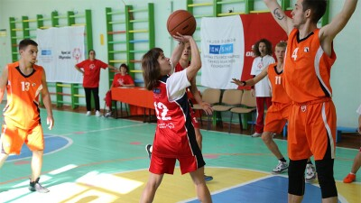 A teenage girl jumps to take a basketball shot as a teenage boy jumps in front of her to block it, while a few teammates and coaches look on. They are on an indoor basketball court with Special Olympics and Stavros Niarchos Foundation banners.