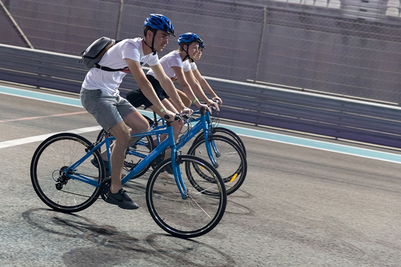 Three volunteer cyclists, side by side, cycle around the course. All three are on blue bikes with matching blue helmets.