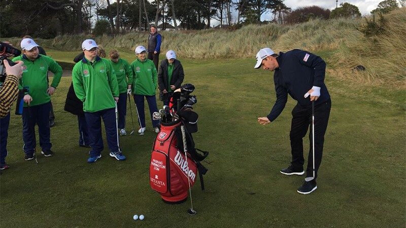 Padraig Harrington playing golf while athletes watch.