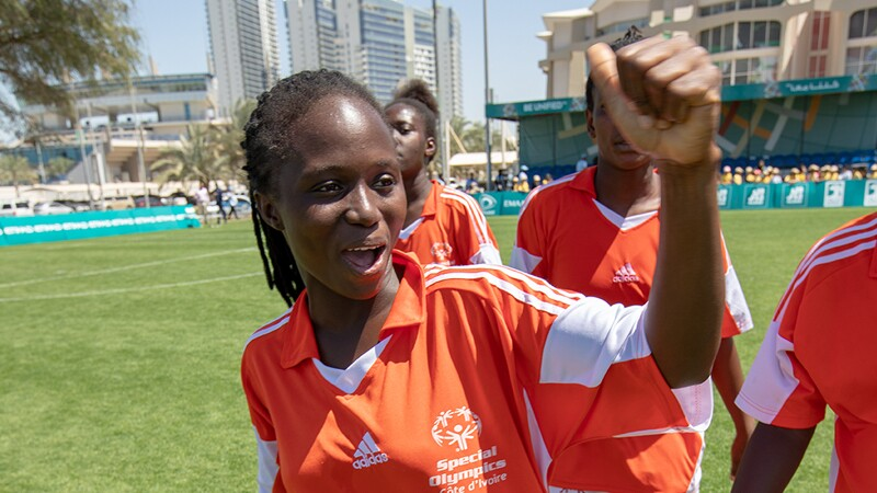 Women's footballer from Cote D'Ivoire give the crowd a thumbs up; her teammates are in the background.