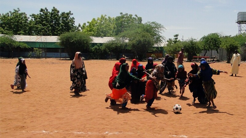 A group of girls and young women playing football on a dirt field.