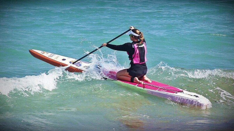 Special Olympics athlete rides stand up paddleboard on her knees.