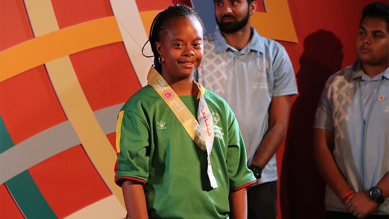 A smile from Team Senegal athlete Khadija Sy after the medal ceremony for the 100m run. She's standing on stage in front of the World Games logo with volunteers behind her.
