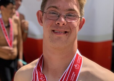 Chris Nikic standing after a swim meet with medals around his neck