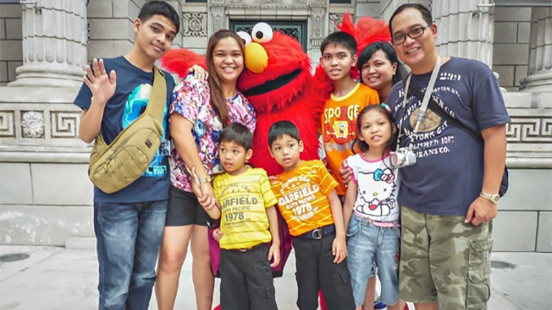 Family of 8 standing together for a photo, Sesame Street's Elmo is standing behind the family.