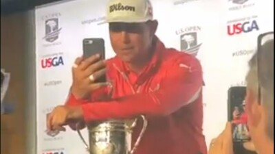 PGA Golf Player on stage looking at his mobile phone and talking to an athlete. Audience member can be seen making a video.