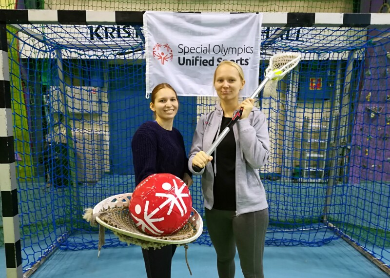 Two girls with Lacrosse stick and ball standing in front of net.