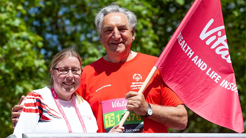 Lyn Dumbleton Special Olympics GB Athlete Leader standing with Jim Carter Actor (Downton Abbey) and Special Olympics GB Ambassador arm around her; both are holing a flag.