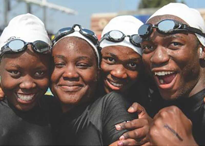 A group of four swimmers in with their arms around one another smiling for a group photo.