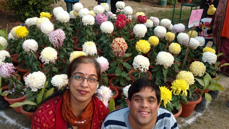 An adult woman and a teenage boy sit together, smiling at the camera, in front of flowers. The woman has her arm around the boy.