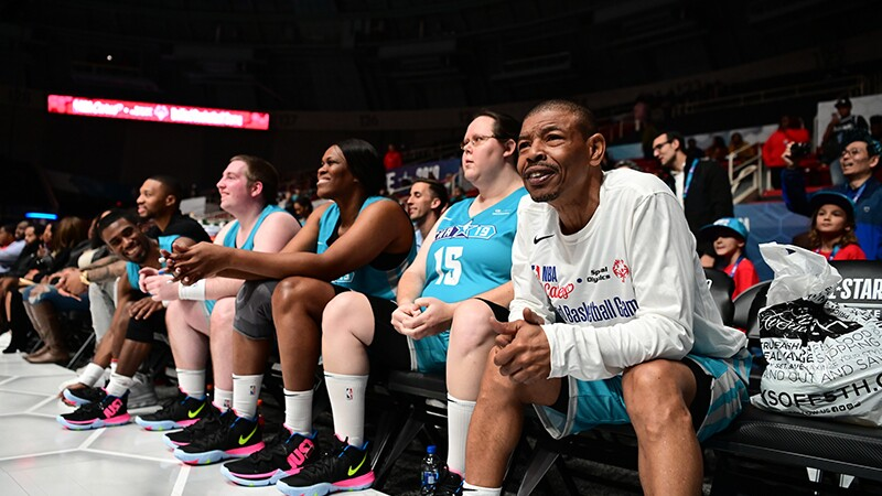 Retired NBA player Muggsy Bogues watches the game, next to him are other athletes and spectators in the background.