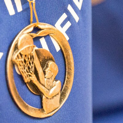 Athlete with a blue Play Unified shirt on and a gold European Basketball medal hanging down.