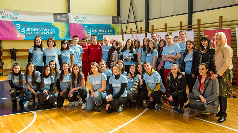 A group photo of athletes, coaches and supporters on two rows in a gym standing in front of Special Olympics banners.