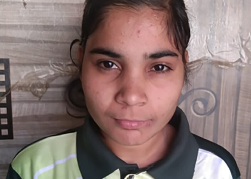 Priyanka, a young girl, stands against a wall in a Special Olympics Bharat Haryana green polo shirt.
