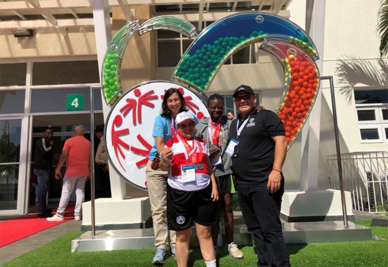 Coach Maria standing in front of the Special Olympics World Tennis Invitational logo installation with two athletes and another coach in front of a pavilion.