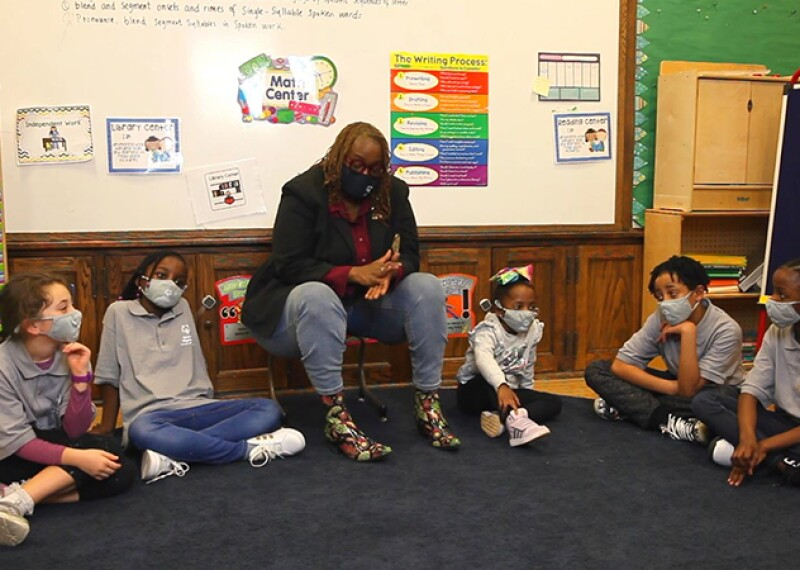 Teacher and 5 students of Bunker Hill Elementary School sitting in a semi circle talking.