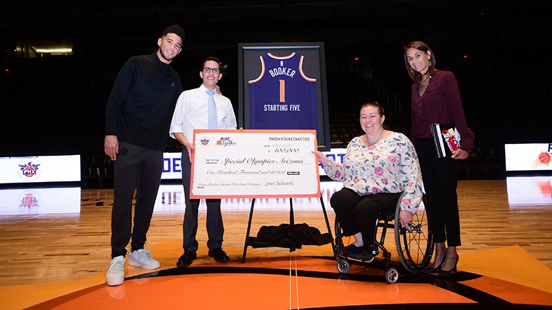Devin Booker and his $100,000 donation check along with with Special Olympics representatives.