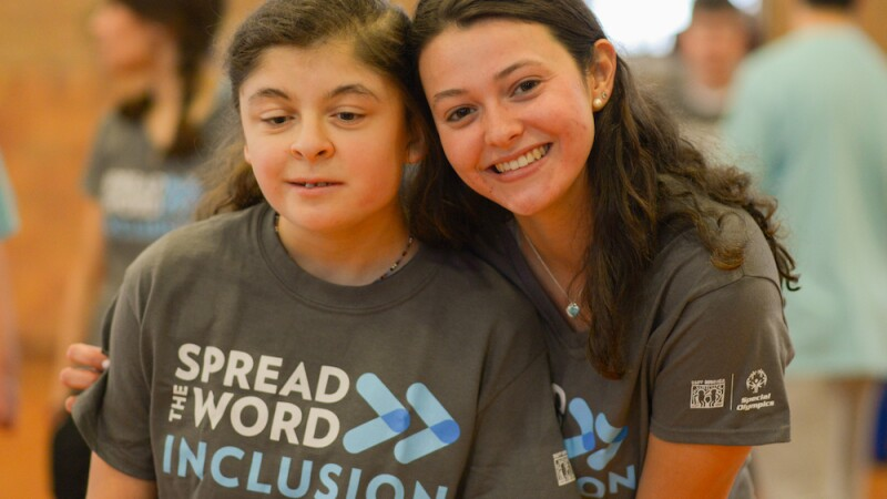 A Special Olympics athlete and youth leader smile together wearing a new Spread the Word Inclusion t-shirt.