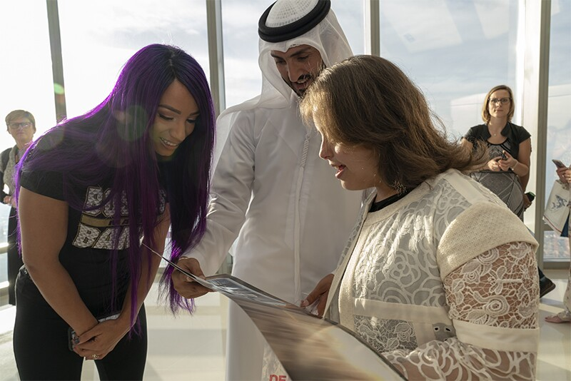 WWE Superstar Sasha Banks and Team UAE athlete Chaica are looking at a visual being shown by a man.