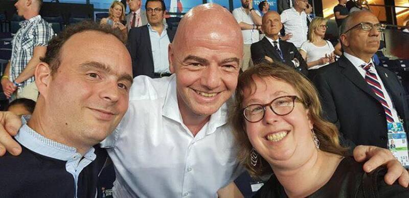 Two men and a women face the camera smiling with a crowd of people in the background. The man in the centre has his arms around the man and woman at either side.