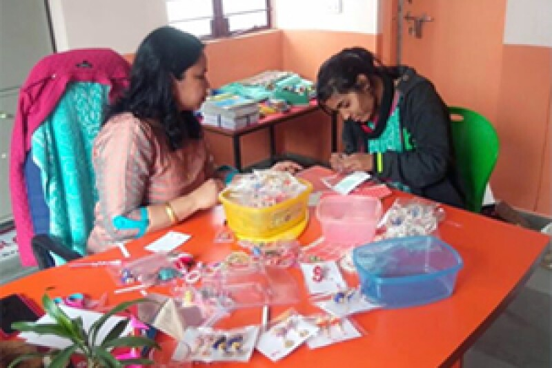 Priyanka and Sunita, an adult woman, sit at a table with a bunch of crafts scattered on it. Sunita watches Priyanka as she works on a craft with her hands.