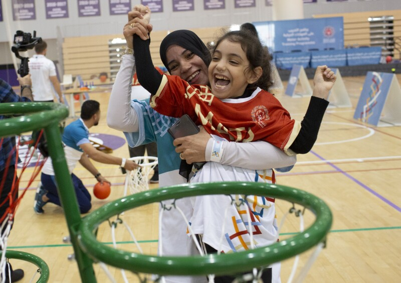 An athlete participating in MATP celebrates with her coach after shooting a basket.