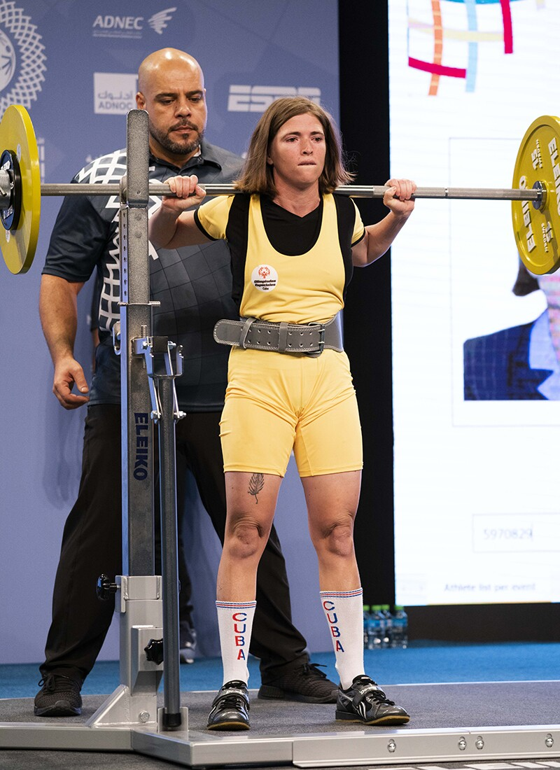 Female power lifter from Cuba in yellow and black holding a bar on her shoulders, a spotter is behind her.