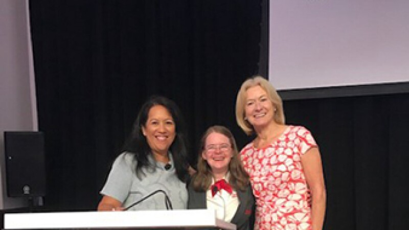 Hanna standing on stage behind a Kantar podium at the New York Stock Exchange with Lynnette Cooke and Mary Davis.