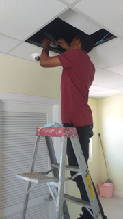 A man in a red shirt stands on a ladder. The upper half of his body is in the ceiling.
