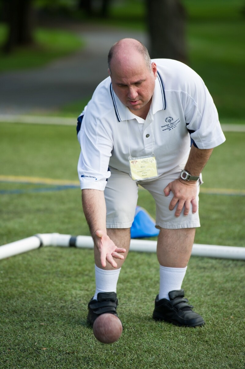 A Special Olympics athlete rolls the bocce ball.