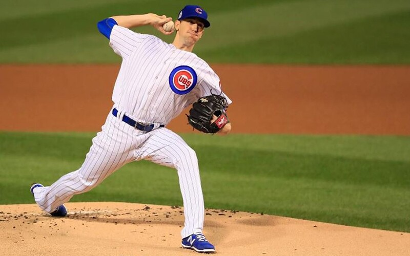 Kyle Hendricks on the pitchers mount wearing his white and blue pin striped Chicago Clubs uniform throwing a pitch.
