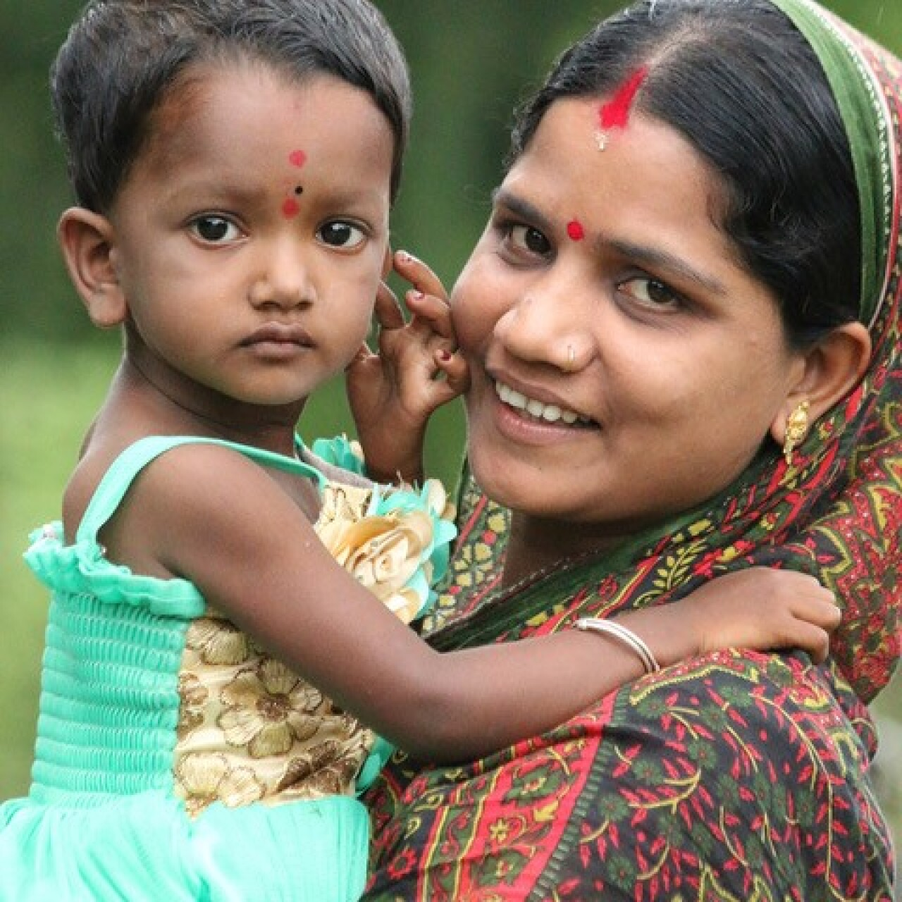 A young woman smiling and looking at the camera; she is wearing a green, black, yellow, and green sari; she is holding a young girl that is wearing a light blue and gold floral dress.