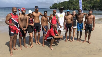 Athletes and coaches pose in front of the open water swim course.