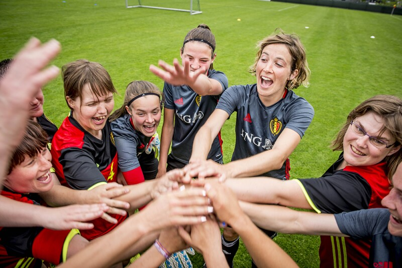 European Football female group on the field standing in circle with all of their hands in the the middle one on top of another in celebration.